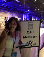 "woman with clipboard and walkie talkie near sign that says ""CAC members & Will Call"""