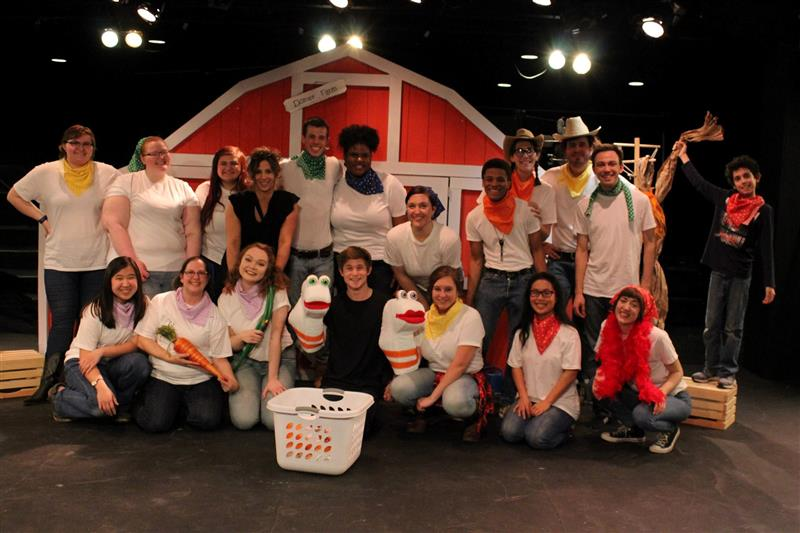 Cast of a theatre show. They all wear white t-shirts and are standing in front of a barn door