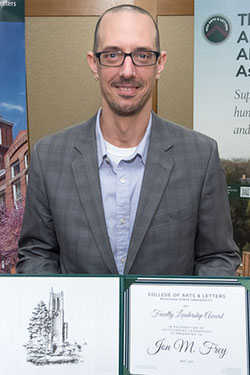 portrait of a man with glasses holding award