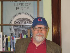 man in front of bookshelf wearing cubs baseball cap