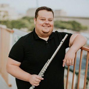 man holding flute leaning on bridge railing